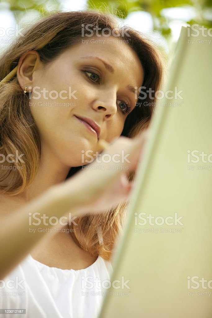 Young woman drawing in park royalty-free stock photo