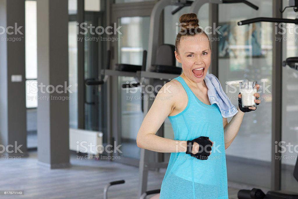 Young woman dressed in a sport uniform keeps milk stock photo