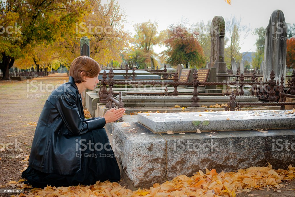 Young woman dressed in black praying at grave in cemetery stock photo