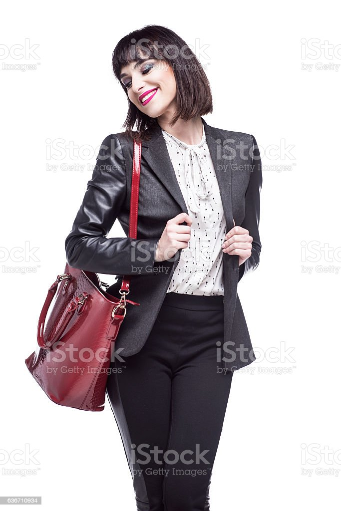 Young woman dressed in business attire holding a red bag. stock photo