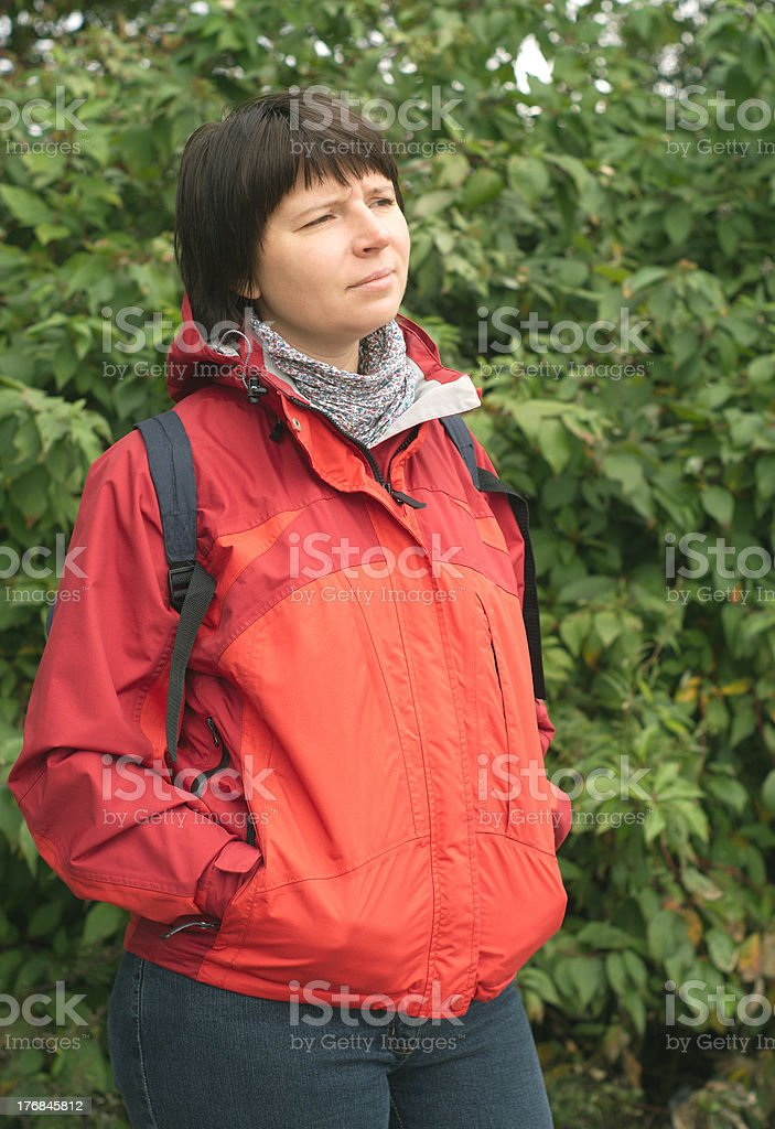 Young woman dressed in red blazer with backpack on nature stock photo