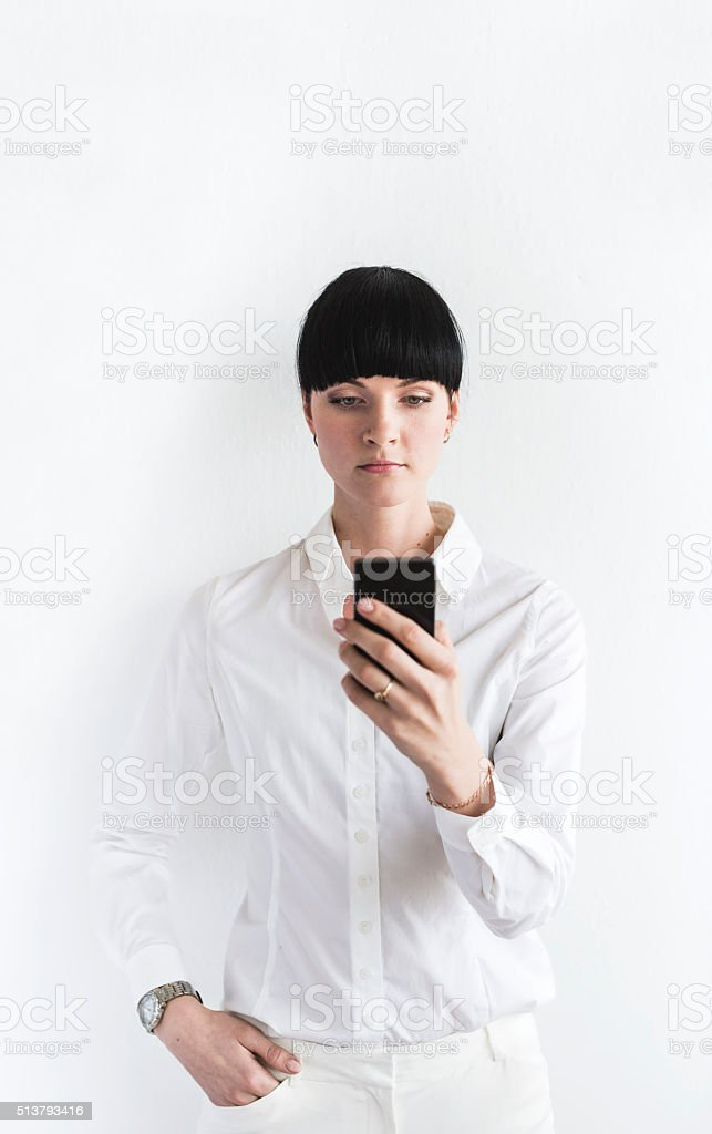 Young Woman Dressed in White Holding Smartphone In Front stock photo