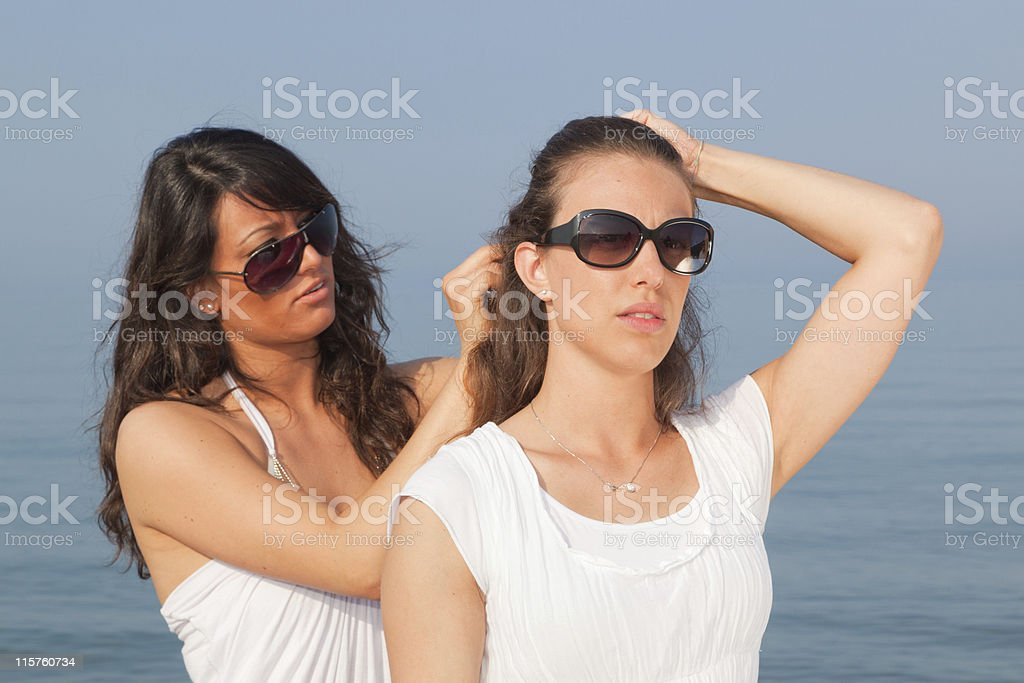 Young Woman Dressing Her Friend's Hairs at Seaside royalty-free stock photo
