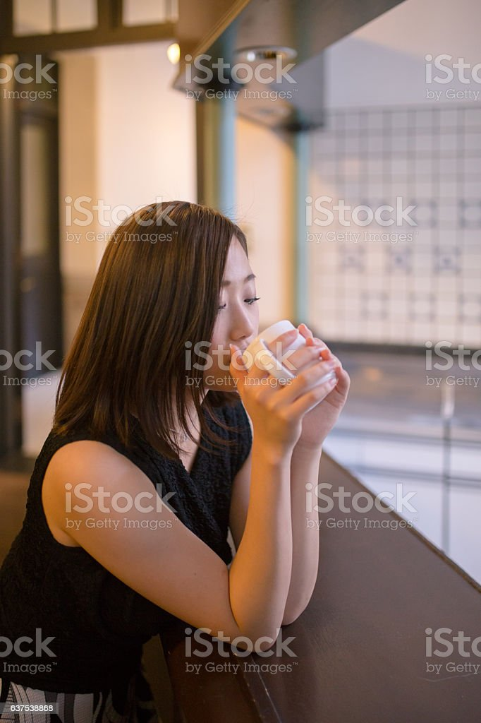Young woman drinking a cup of coffee at bar counter stock photo