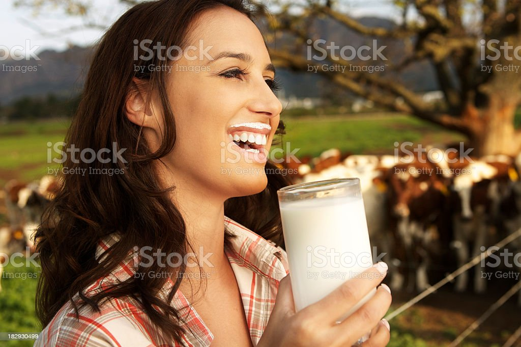Young woman drinking a glass of milk on a dairy farm stock photo