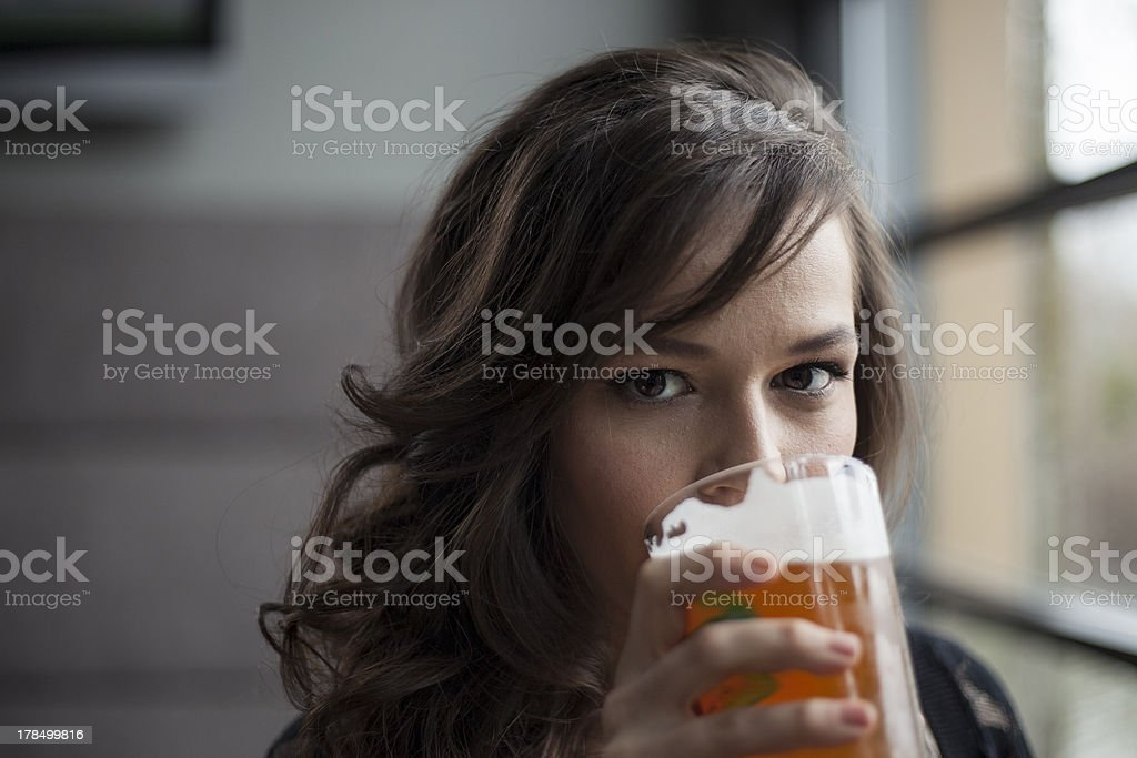 Young Woman Drinking a Pint Glass of Pale Ale stock photo
