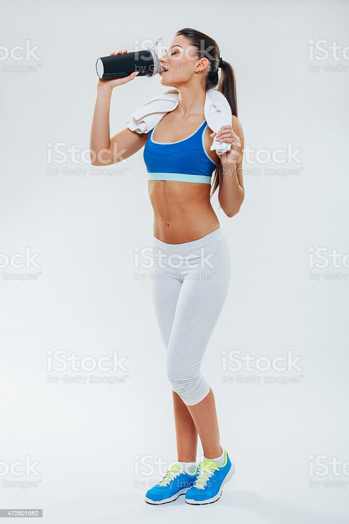 A young woman drinking a sports drink after working out stock photo