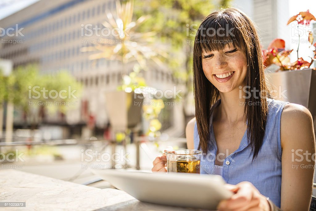 young woman drinking a tea on the city and surfing stock photo