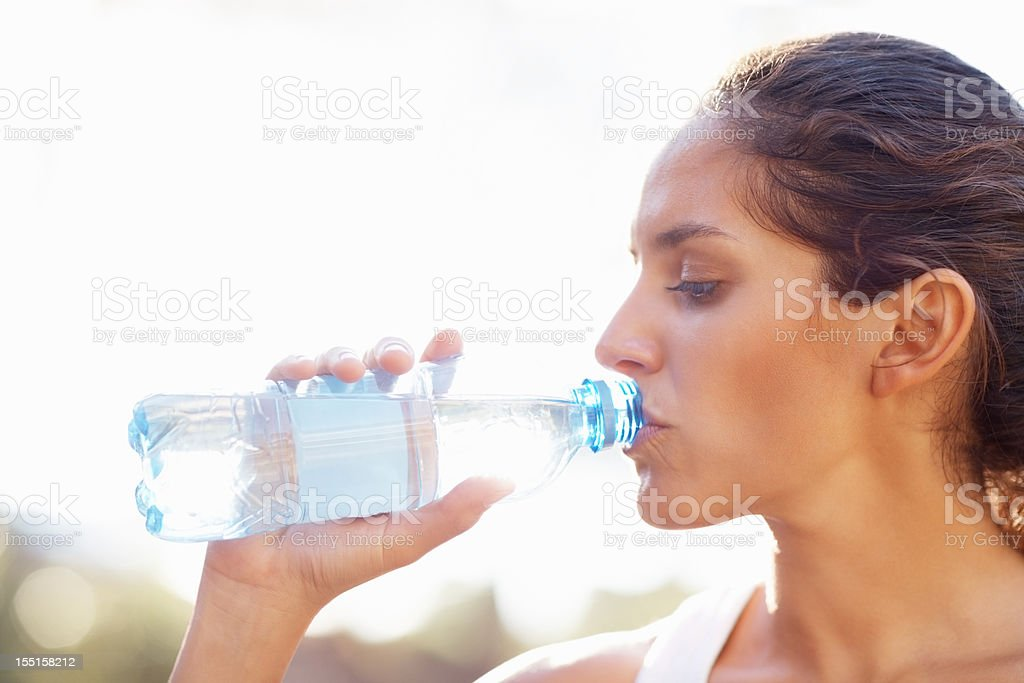 Young woman drinking bottled water royalty-free stock photo