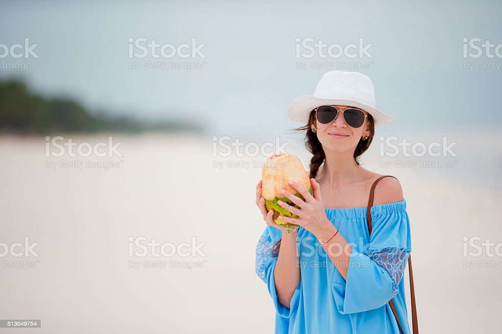 Young woman drinking coconut milk during tropical vacation stock photo