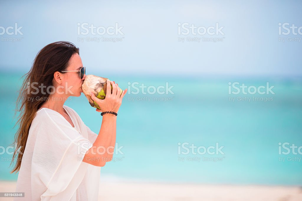 Young woman drinking coconut milk on the beach stock photo