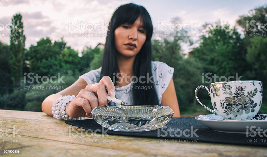 Young woman drinking coffee and smoking cigarette outdoors stock photo
