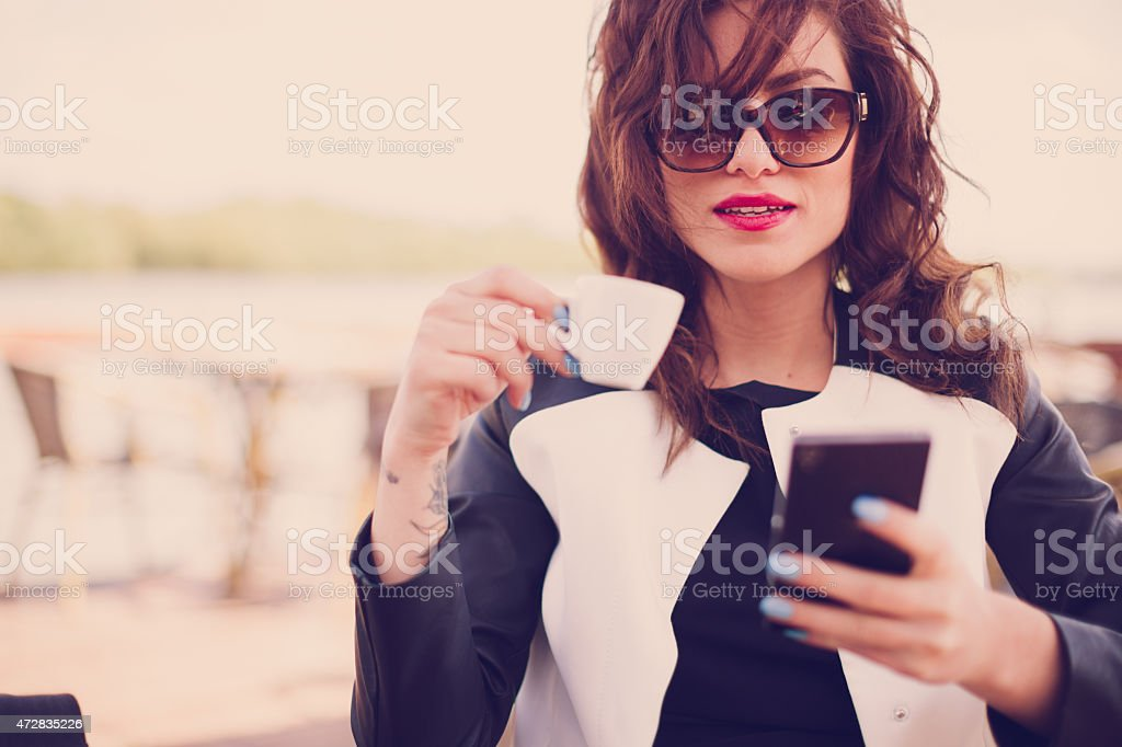 Young woman in cafe, drinking coffee and using her mobile phone