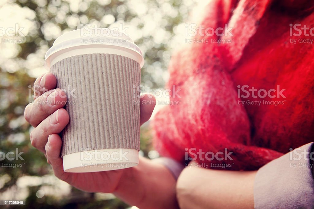 Young woman drinking coffee from disposable cup stock photo