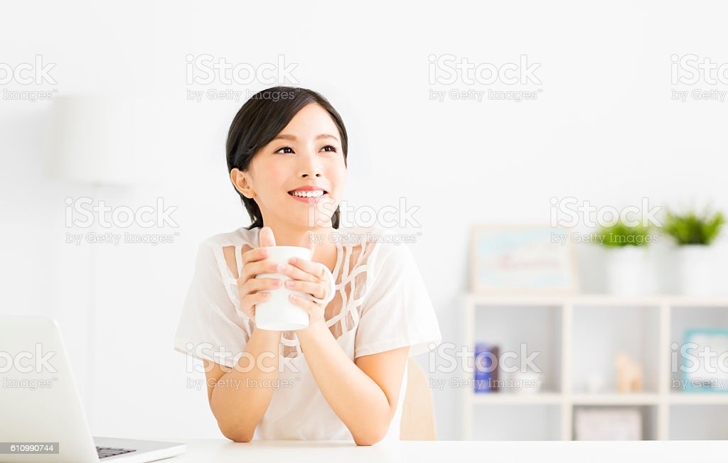 young Woman drinking  coffee in living room stock photo