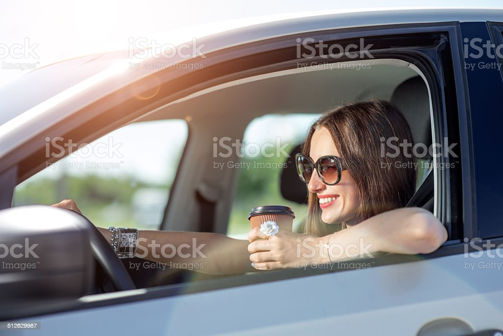 Young woman drinking coffee while driving her car stock photo