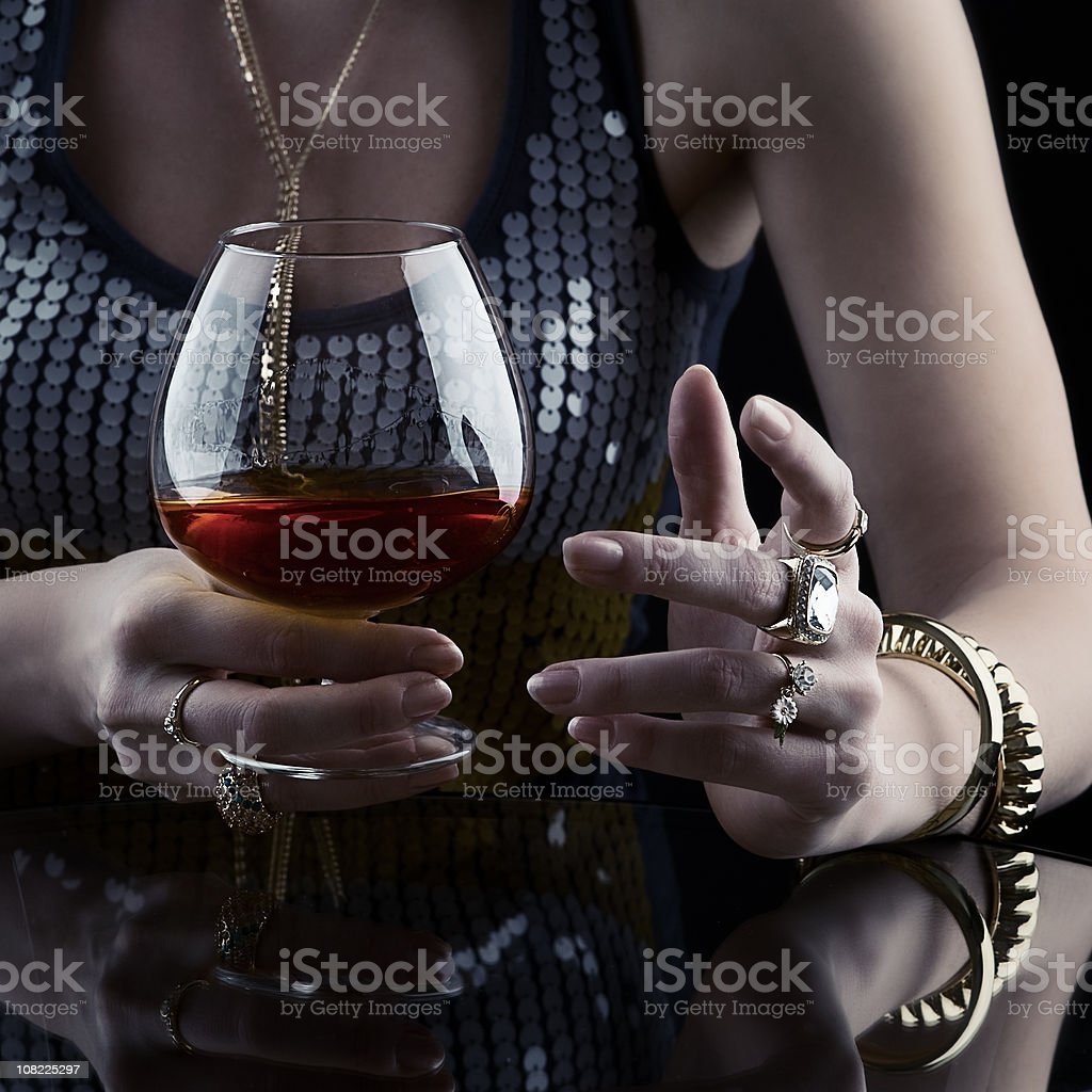 Young Woman Drinking Cognac and jewelry stock photo