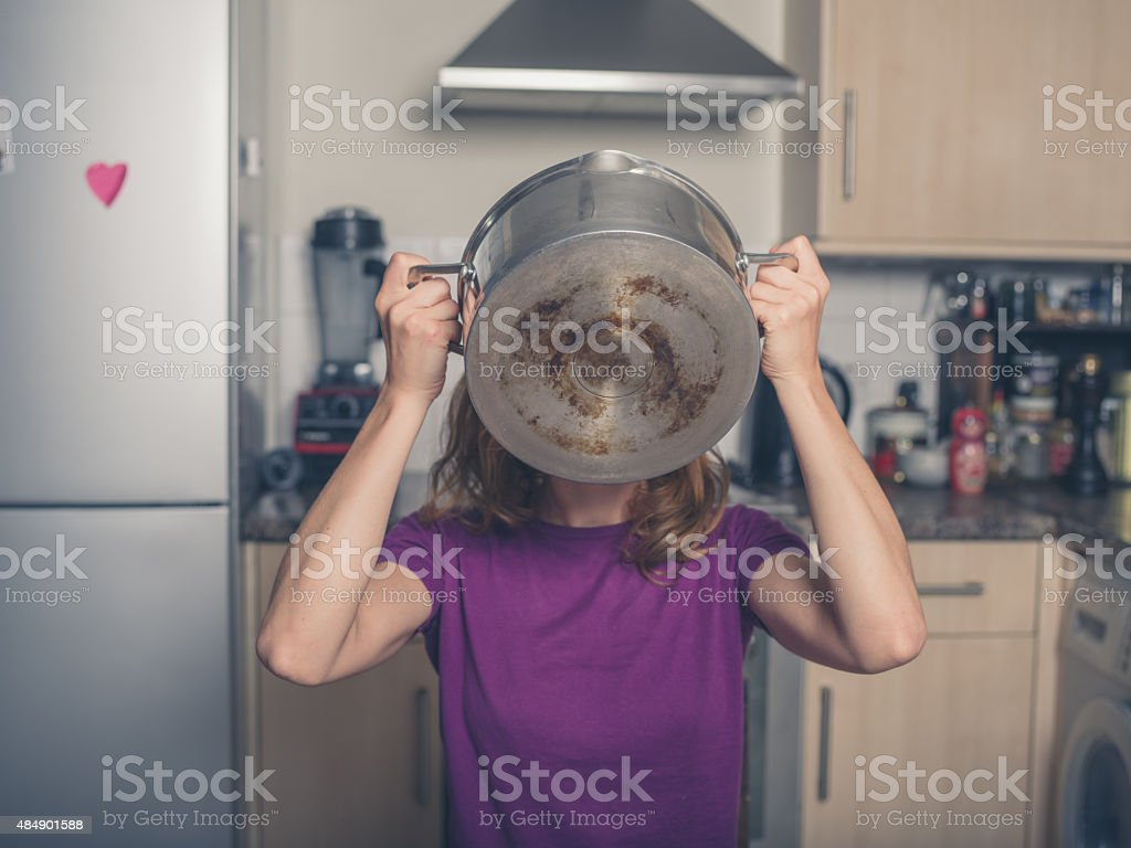 Young woman drinking from pot in kitchen stock photo