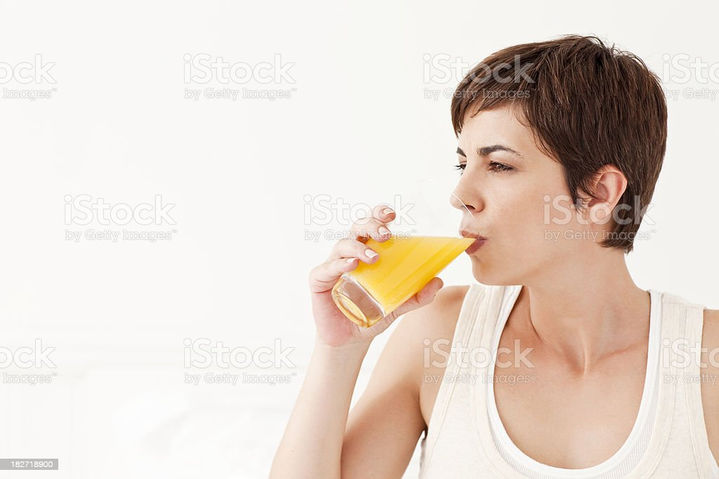Young Woman Drinking Glass of Orange Juice royalty-free stock photo