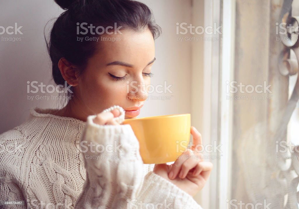 Young woman drinking hot coffee near the window stock photo