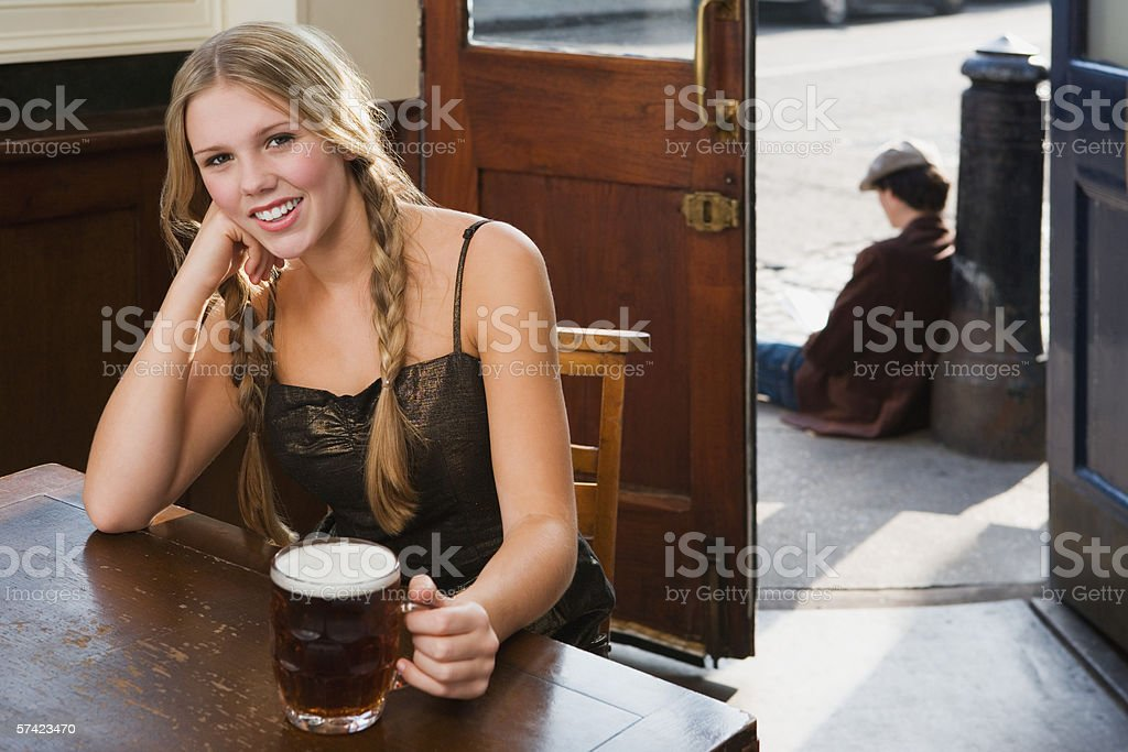 Young woman drinking in pub stock photo