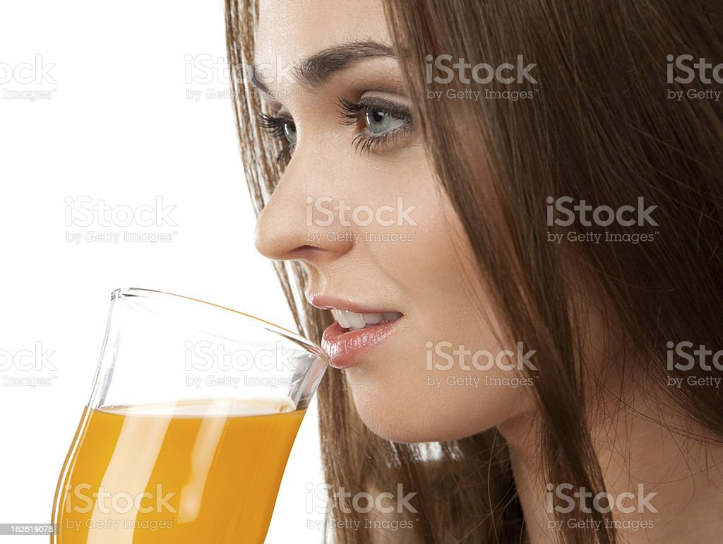 Young woman drinking juice, on the white background royalty-free stock photo