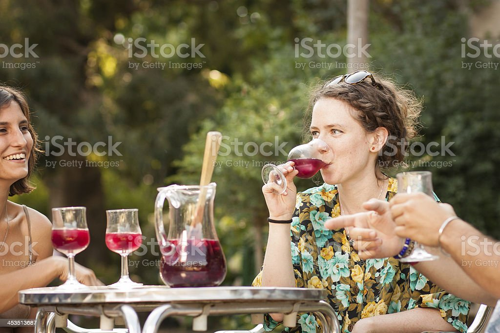 Young woman drinking sangria with friends stock photo