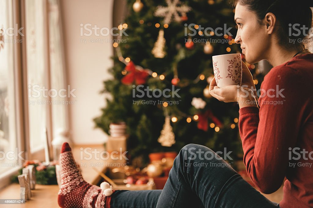 Young woman drinking tea by the Christmas tree stock photo
