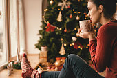 Young woman drinking tea by the Christmas tree