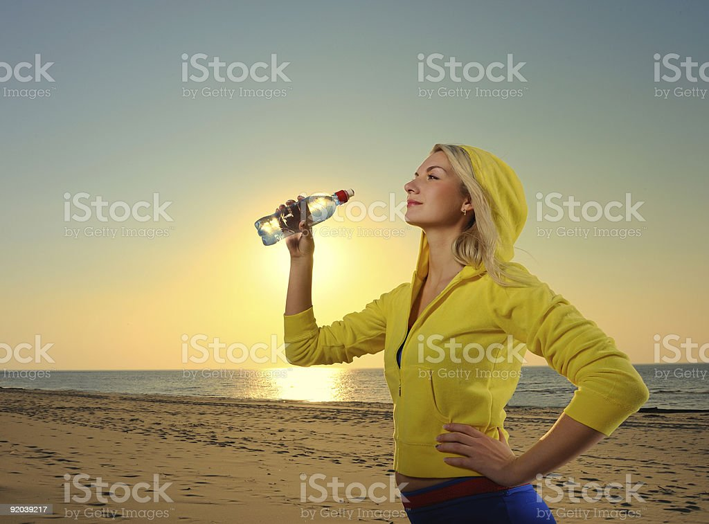 Young woman drinking water after fitness exercise royalty-free stock photo