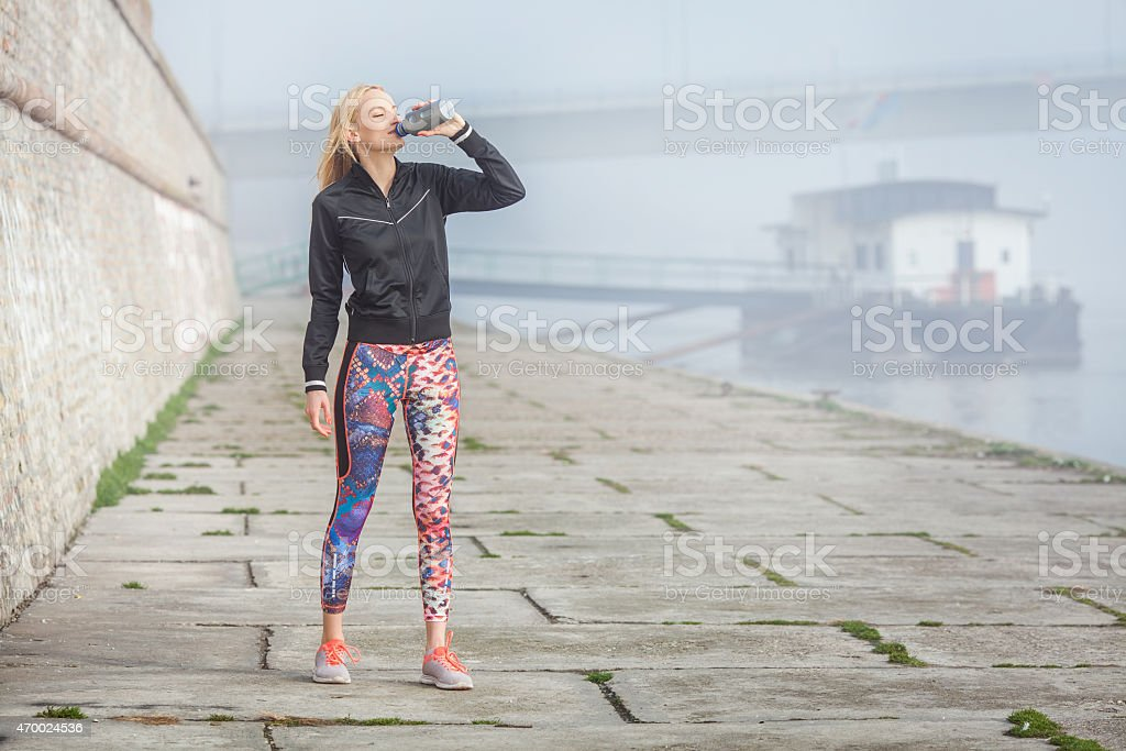 Young Woman Drinking Water   After Jogging stock photo