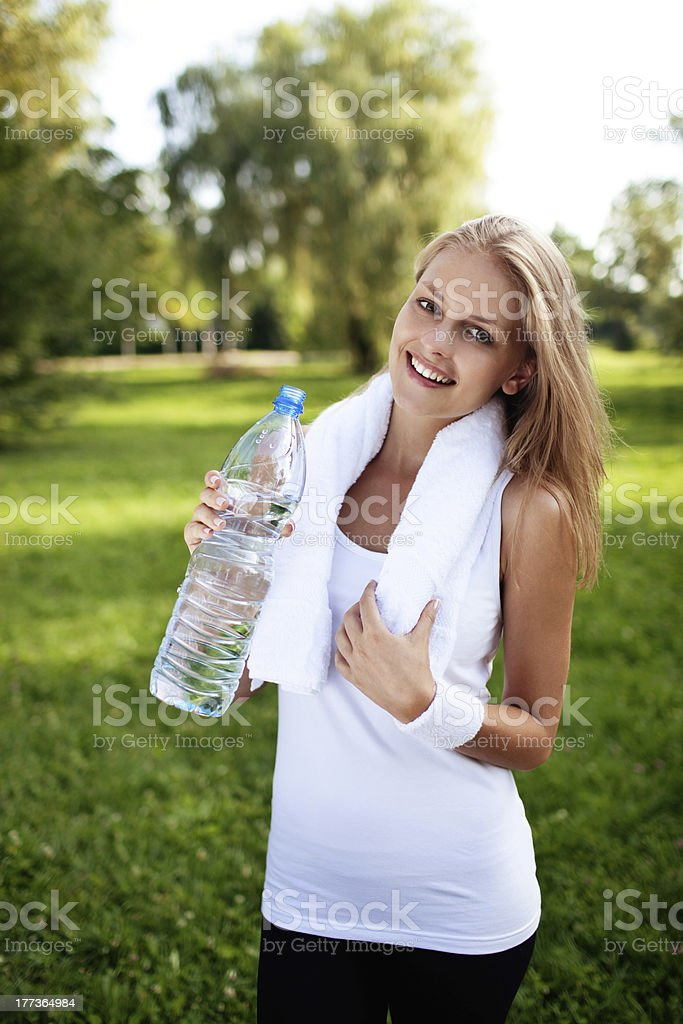 Young woman drinking water after training stock photo