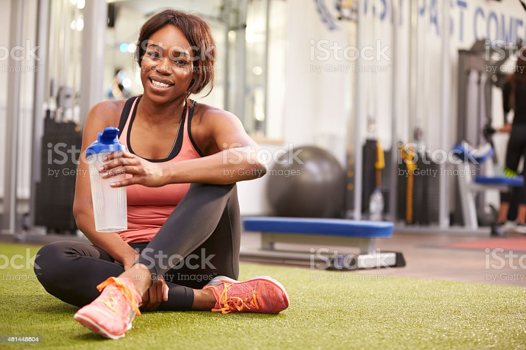 Young woman drinking water in a gym, with copy space stock photo