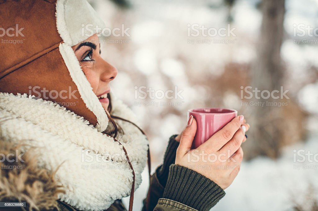 Young woman drinks a hot beverage in the winter stock photo
