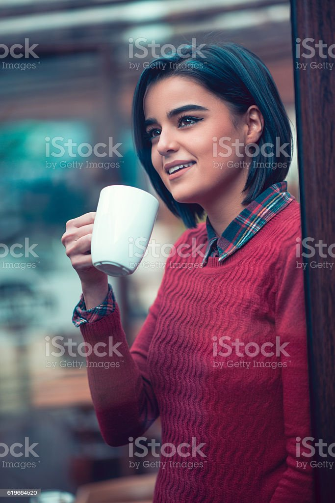 Young Woman Drinks Coffe and Looking Through Window in Cafe stock photo