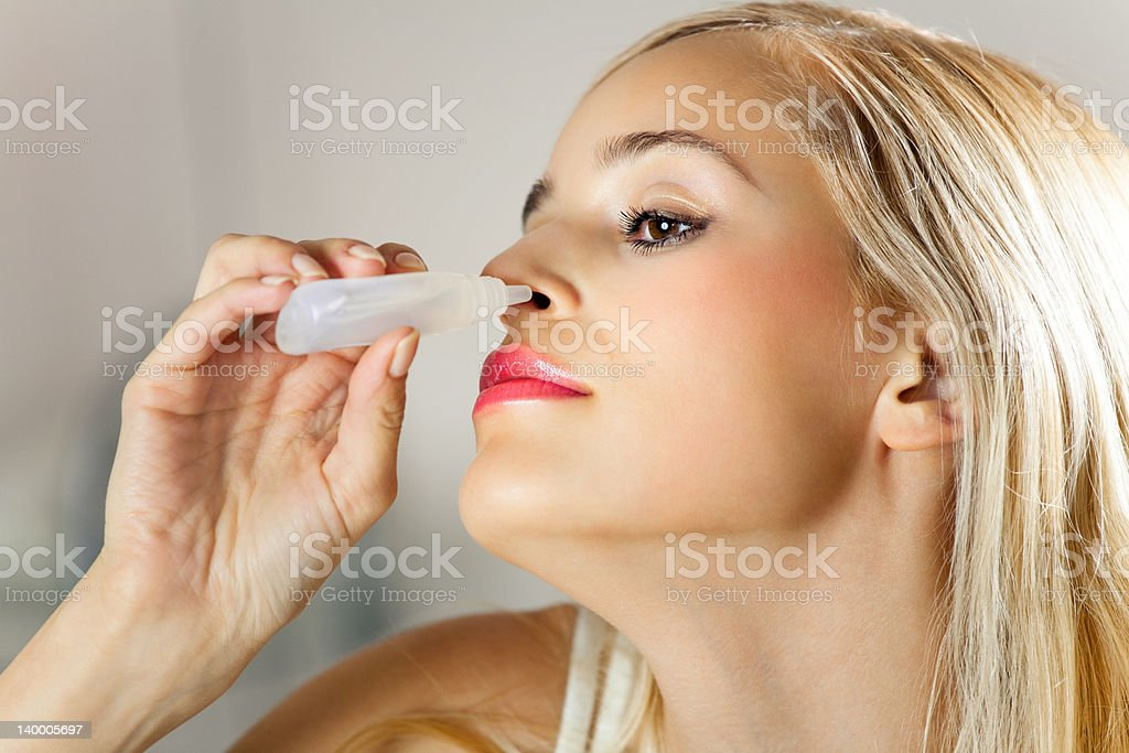 Young woman dripping nose at home stock photo