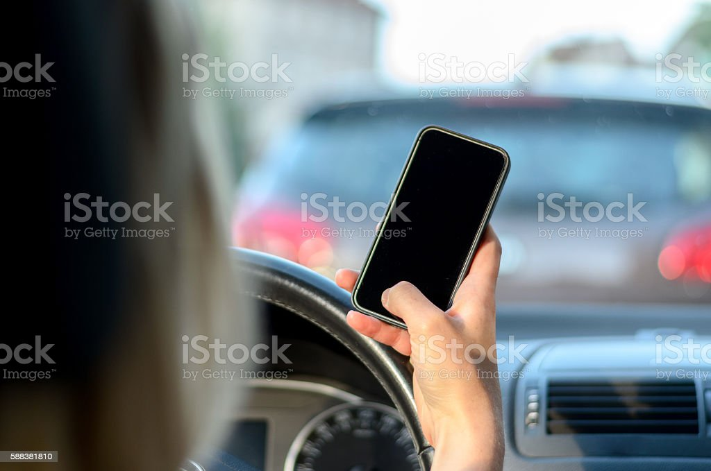 Young woman driver reading a text message stock photo