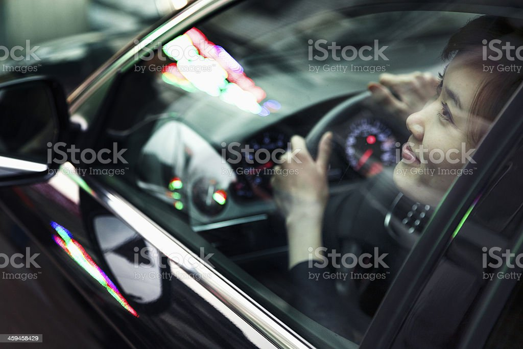 Young woman driving and looking through car window stock photo