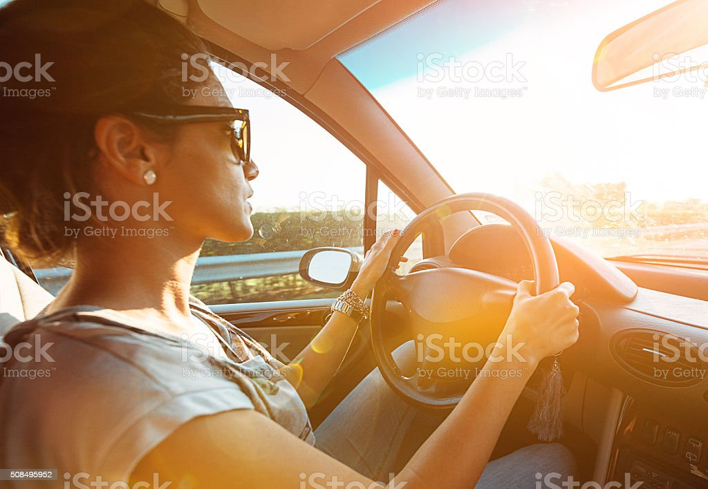 Young woman driving car and speeding on highway in summer stock photo
