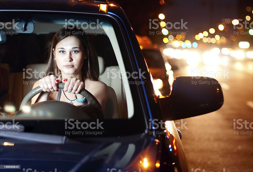 Young woman driving car in the night city stock photo