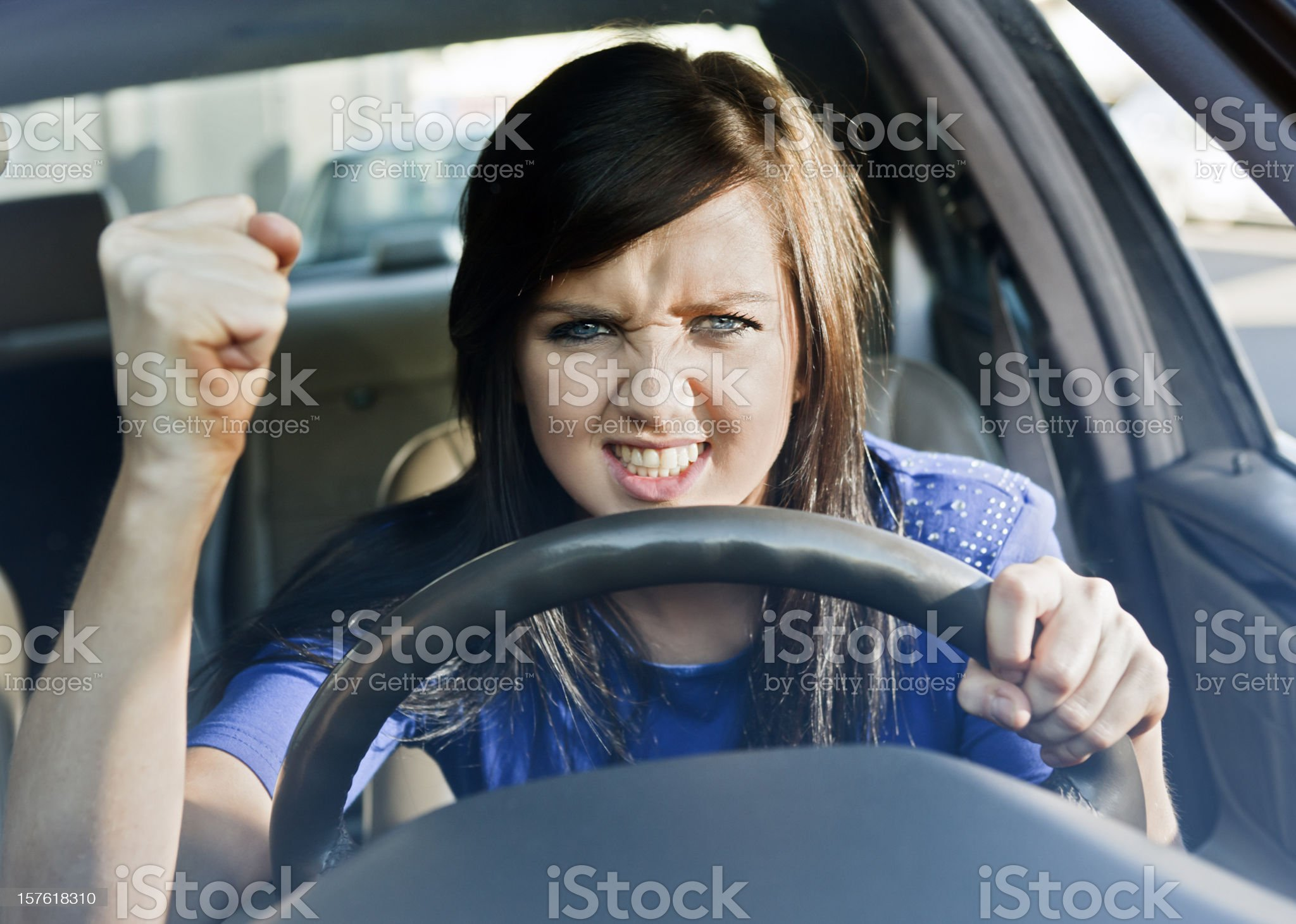 Young woman driving car shakes her fist in frustrated fury royalty-free stock photo