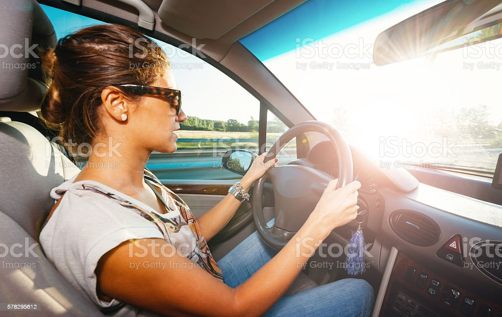 Young woman driving city car in summer on highway stock photo