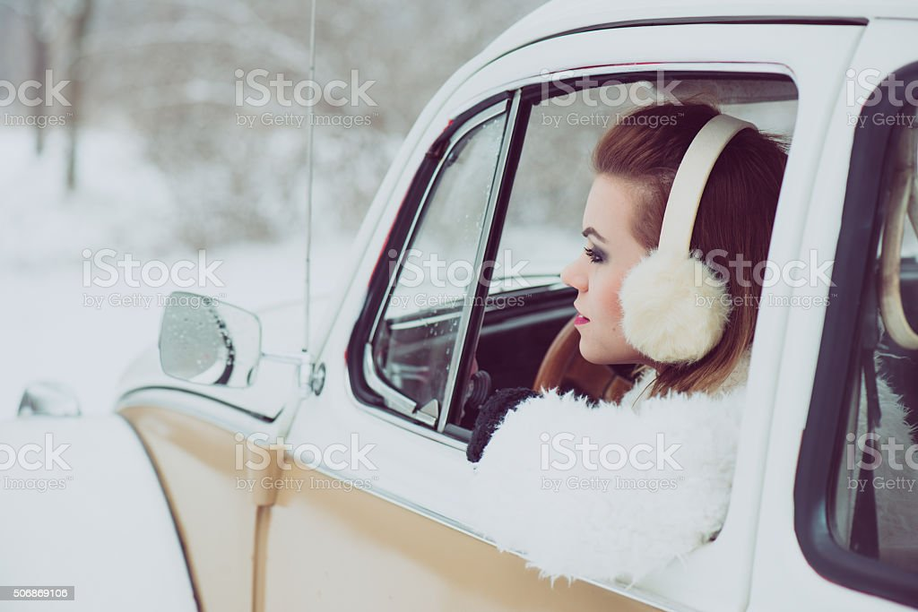 Young woman driving vintage car at snowy road stock photo