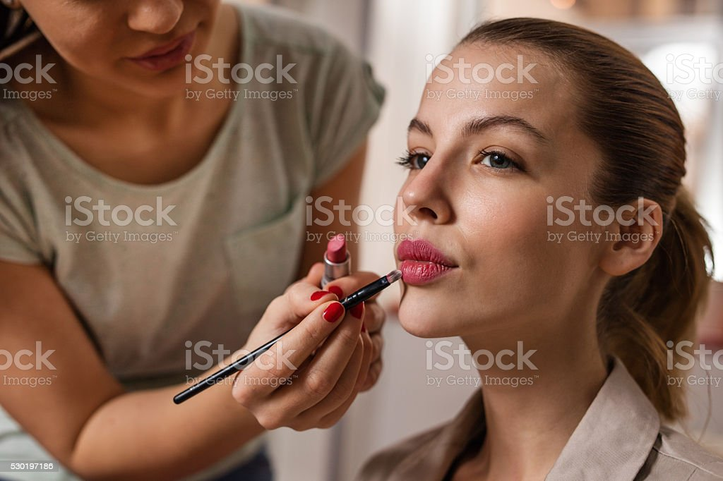 Young woman during make-up treatment. stock photo