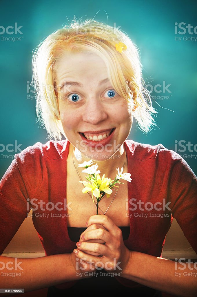 Young Woman Eagerly Smiling and Holding Flowers stock photo