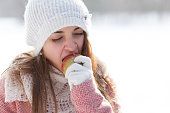 Young woman eating apple in the winter
