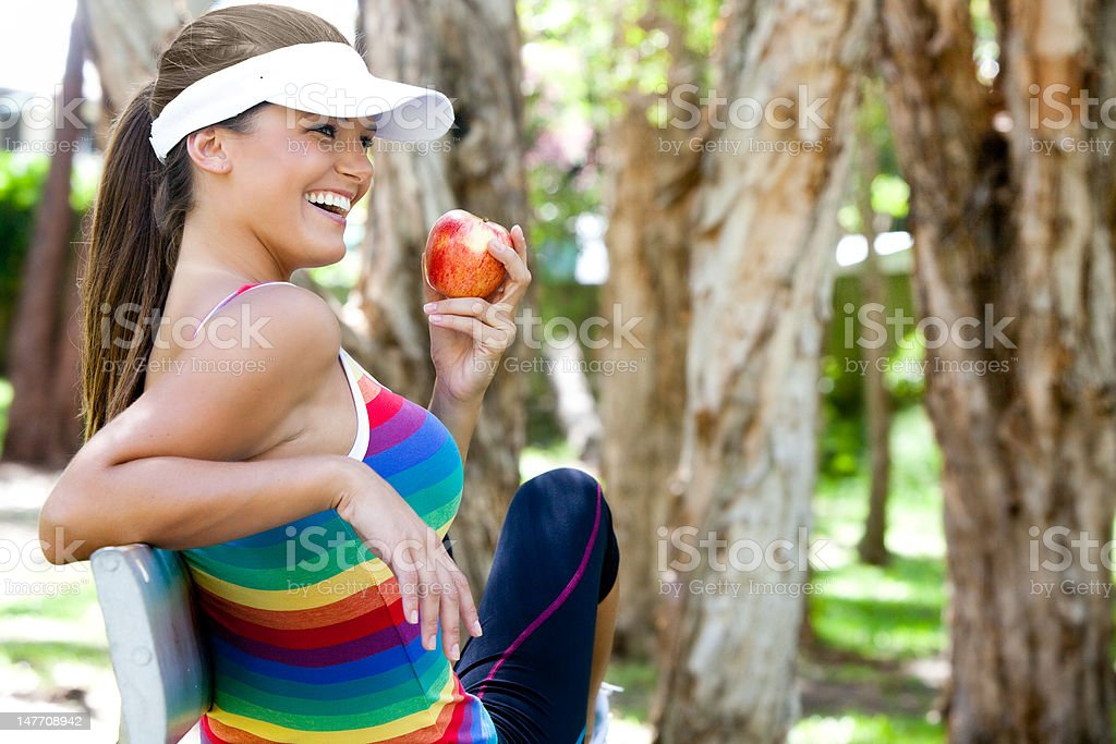 Young Woman Eating Apple on Park Bench stock photo
