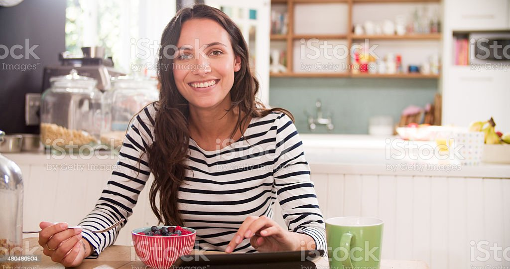 Young Woman Eating Breakfast Whilst Using Digital Tablet stock photo