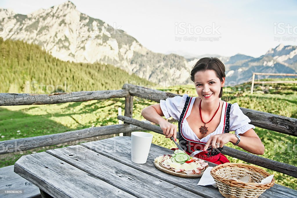 Young Woman eating Brettljause stock photo