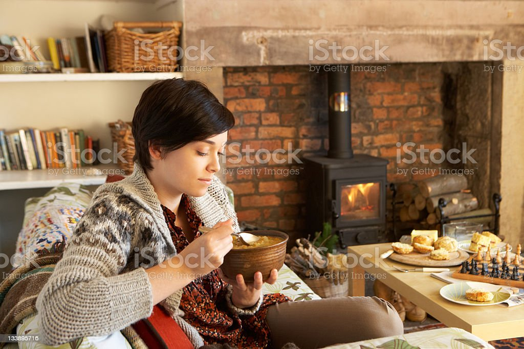 Young woman eating by fire stock photo